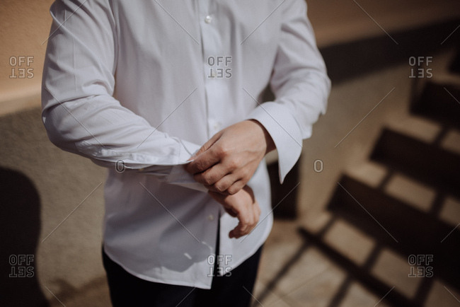 Groom buttoning sleeve on his shirt