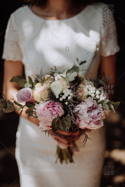 Bride holding bouquet with peonies and calla lilies