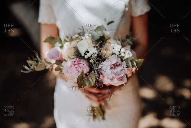 Close up of bride holding bouquet with peonies and calla lilies