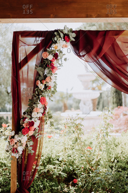 Wedding arbor with red curtains and flowers