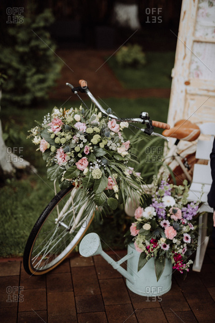 Floral arrangements in a watering can and on an old bicycle