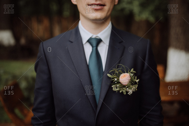 Close up of groom wearing peony boutonniere