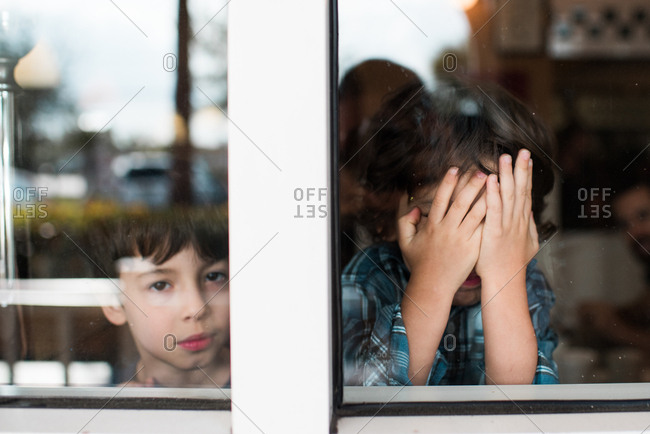 Two boys at window with one covering his face