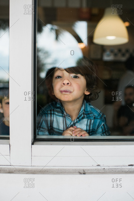 Boy pressing his lips against glass window