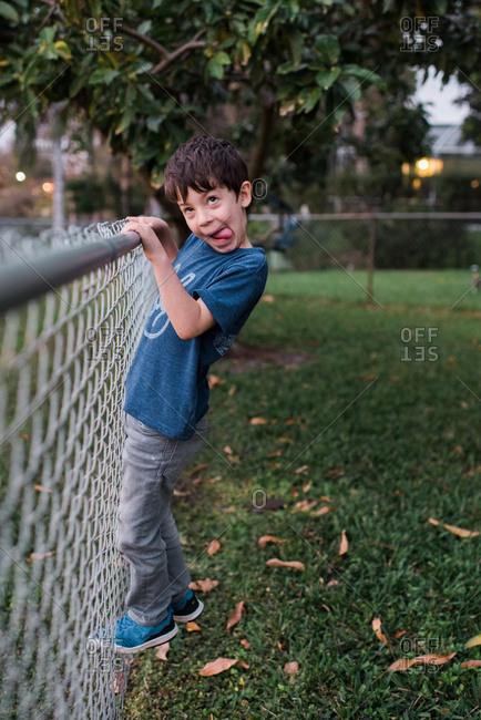 Young boy climbing a fence while making a silly face