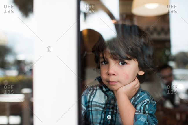 Portrait of cute young boy looking through window