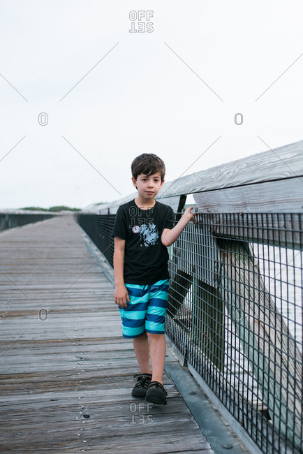 Young boy walking on fishing pier