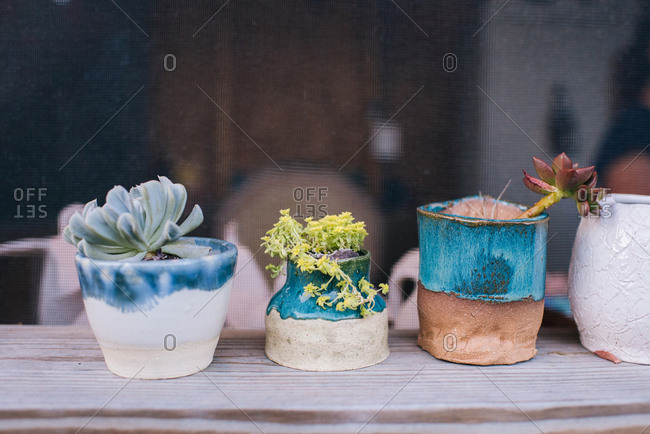 Plants in handmade pots on windowsill