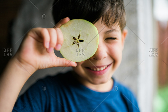 Boy holding an apple slice up to his eye