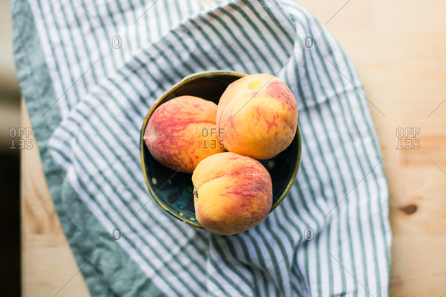 Fresh peaches in a pottery bowl