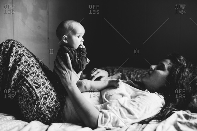 Mother holding young baby on bed