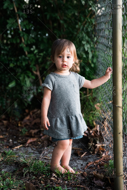 Portrait of toddler girl standing by fence