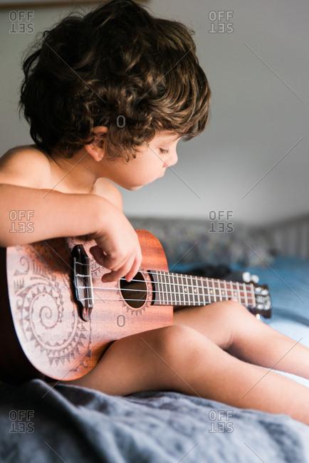 Child playing four-string ukulele