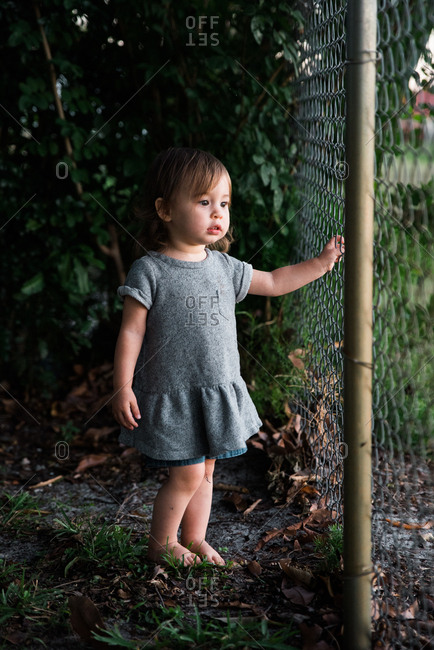 Toddler girl with bare feet looking through fence
