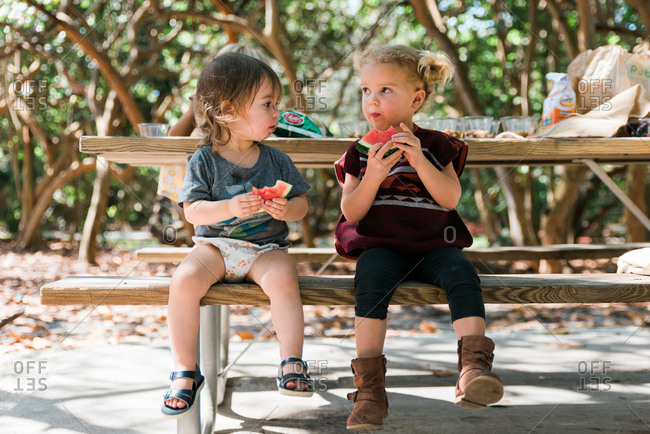 Two toddlers sitting on bench eating watermelon