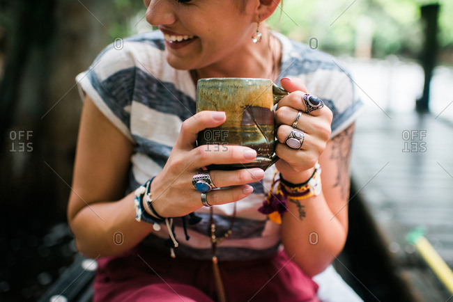 Laughing young woman with chunky rings holding a coffee mug
