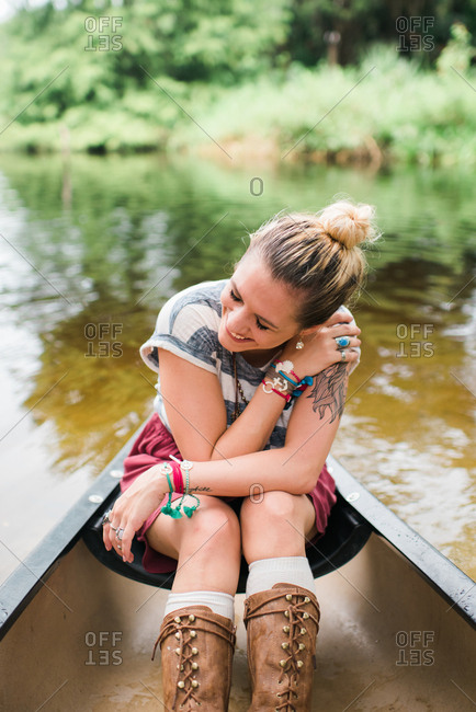 Laughing young woman with tattoo in canoe