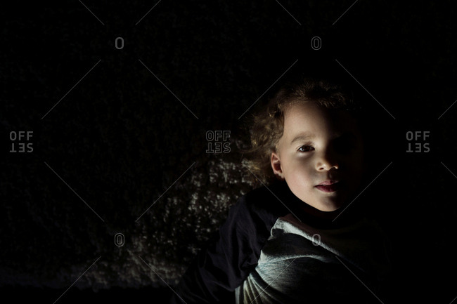 Portrait of a child with curly hair in lowlight