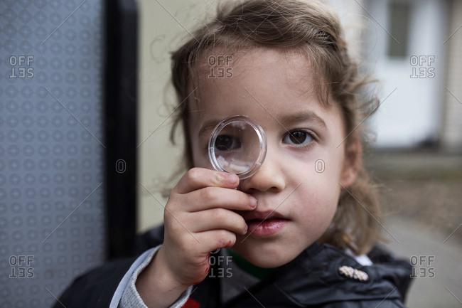 Toddler boy looking through toy magnifying glass