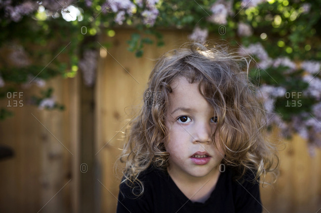 Toddler boy with curly blonde hair and brown eyes outdoors