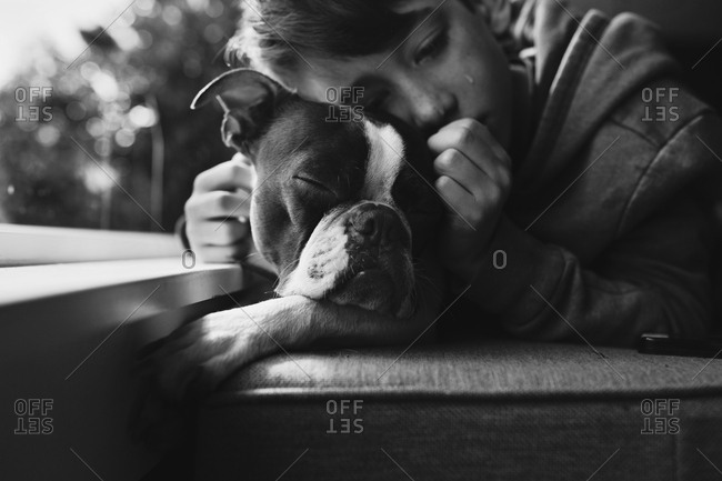 Sad boy hugging his dog in black and white