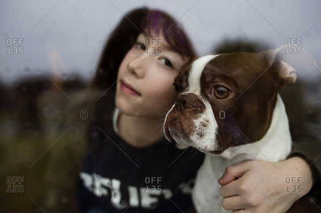 Boy with arm around dog looking out window