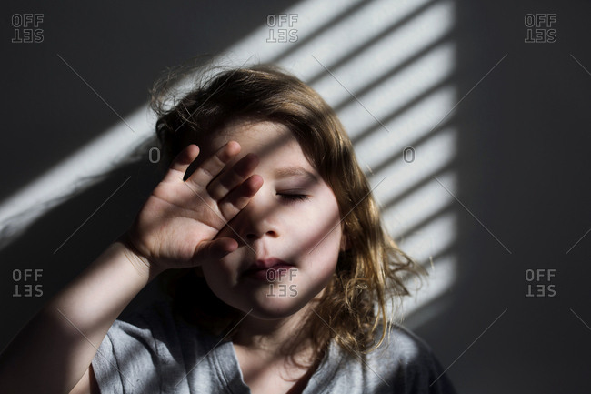Little boy with curly hair covering eye while standing in window light