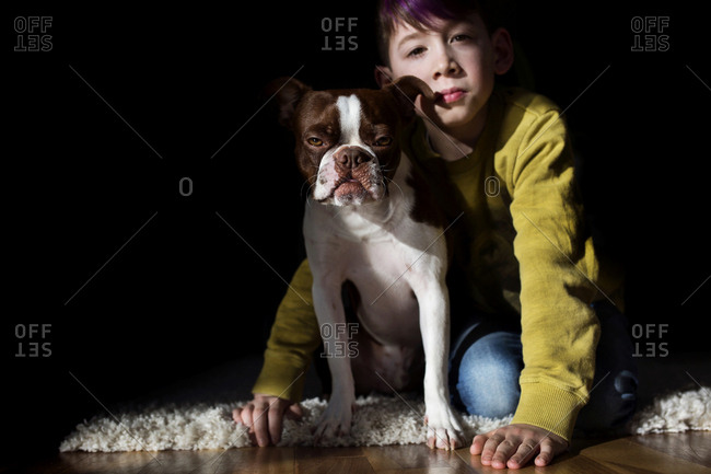 Boy and his dog sitting on carpet