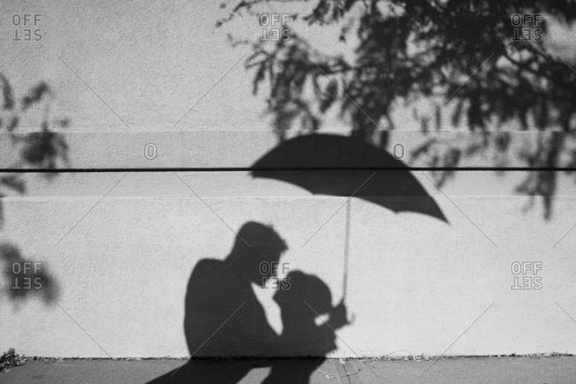 Shadow on wall of bride and groom under umbrella