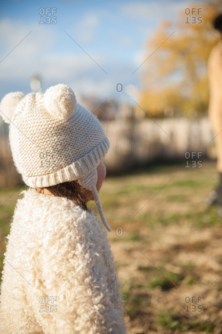 Back view of toddler in faux fur coat and hat with pom pom ears