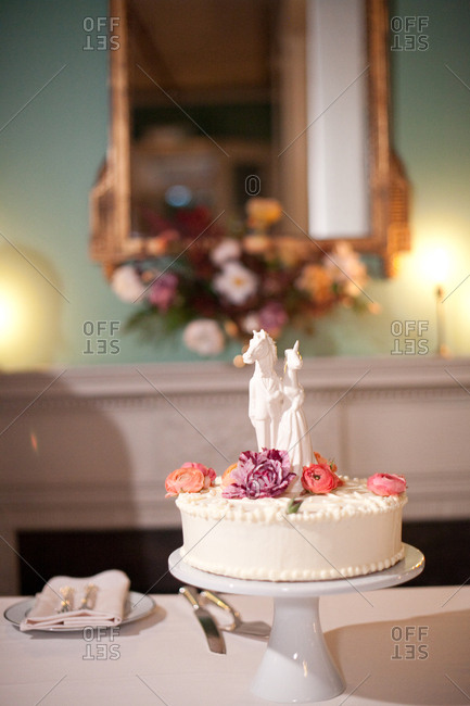 Wedding cake decorated with flowers and unicorn and horse figurine