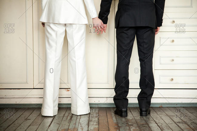 Waist-down show of a couple holding hands on their wedding day