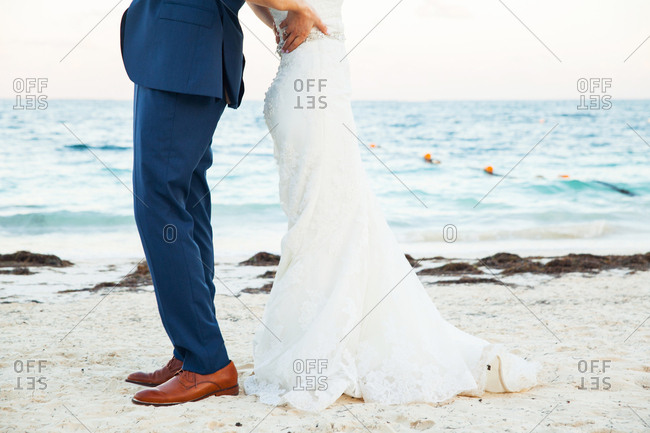 Bride and groom standing back-to-back on beach