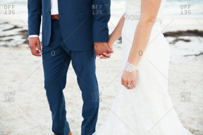 Waist-down portrait of bride and groom holding hands on beach