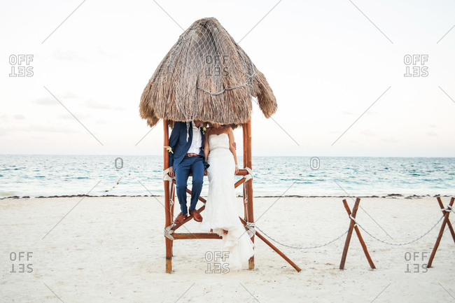 Bride and groom sitting on lifeguard stand at beach