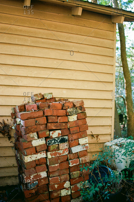 Pile of bricks stacked along side of house