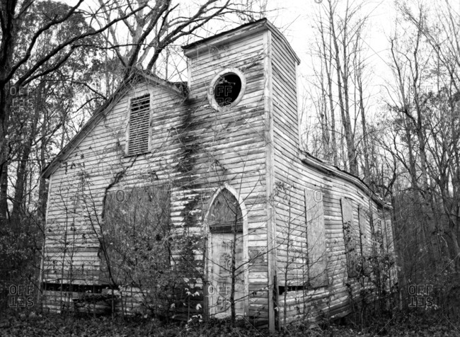 Abandoned church building overgrown with trees