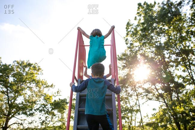 Children climbing up the ladder of a slide