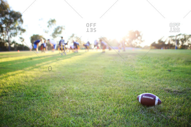 Football in middle of football field with team in background