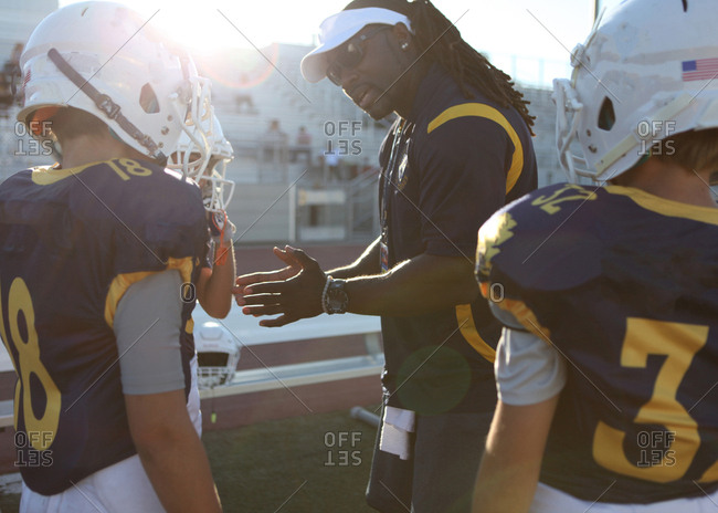 Coach talking to young football players