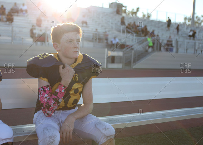Boy sitting on the bench during a football game
