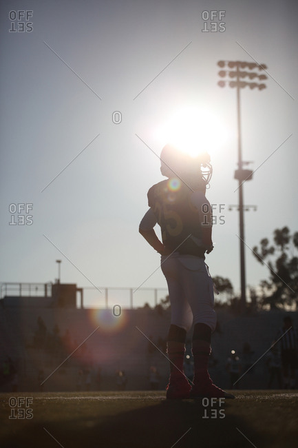 Silhouette of a young football player on the field