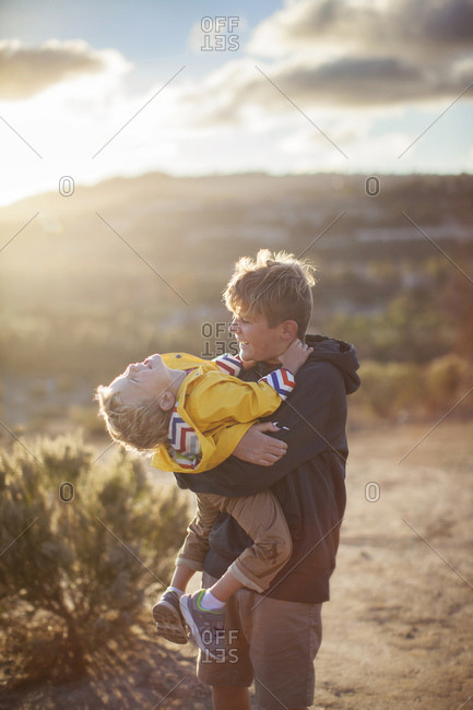Toddler boy and tween brother hugging and laughing