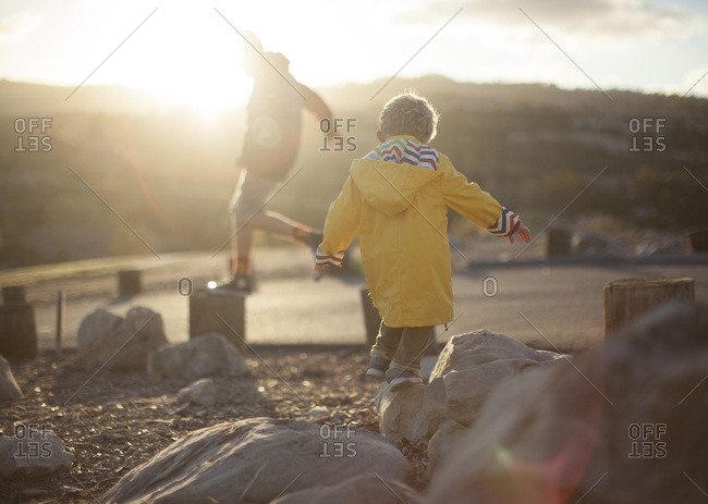 Toddler and tween brothers playing on rocks on a hill
