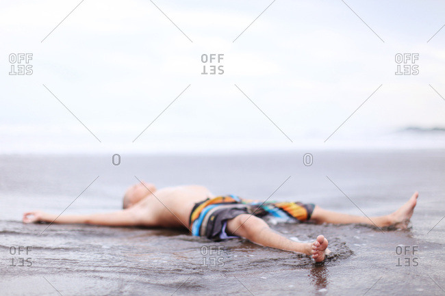 Boy laying in the sand and water at the beach