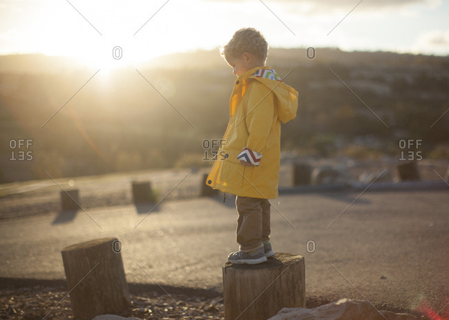 Toddler boy in a raincoat standing on a log
