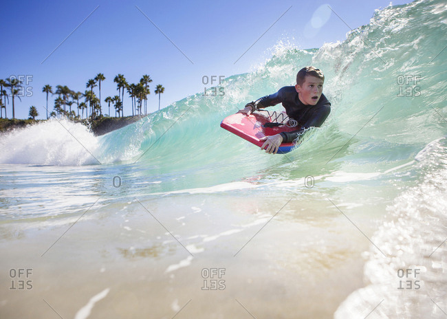Boy body boarding in the waves with palm trees behind