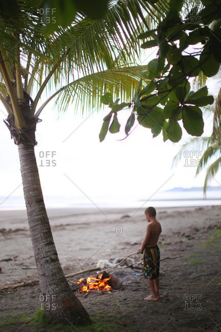 Boy under palm tree stirring fire on a beach