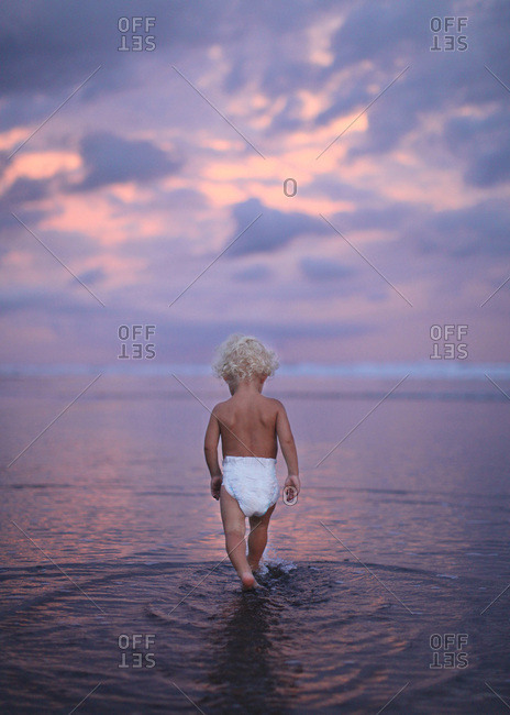 Baby walking in the water on a beach at sunset