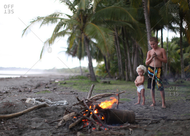 Two brothers watching a fire on a deserted beach